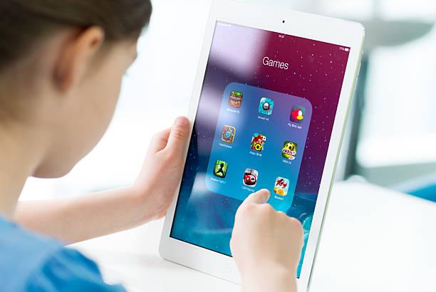 Kind hält ein iPad und hält einen Finger Richtung Bildschirm